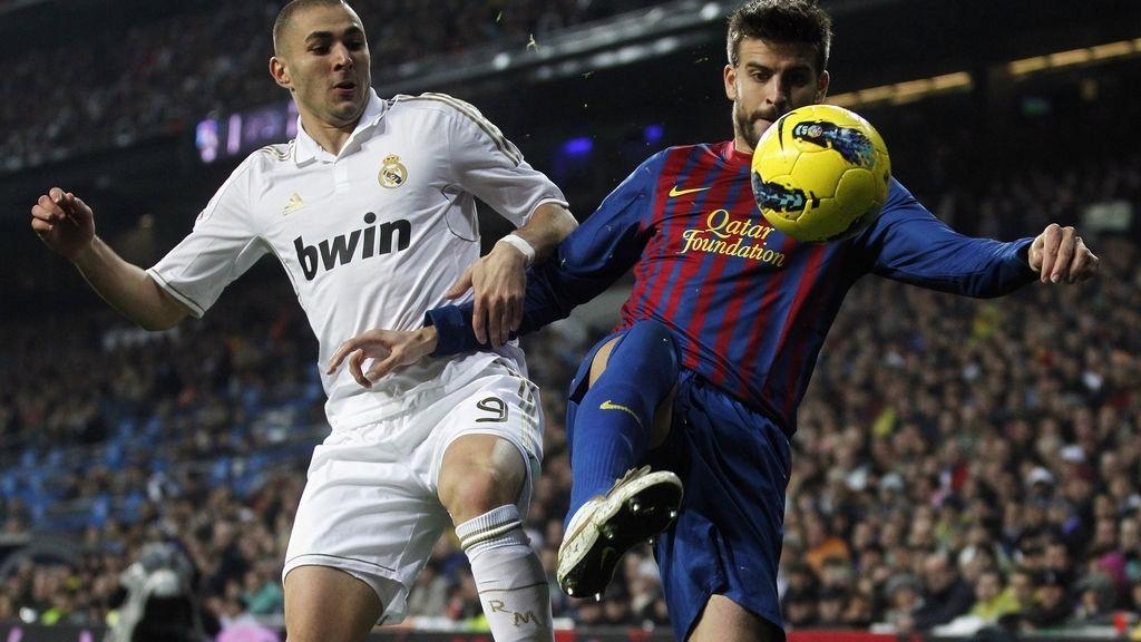 Benzemá y Piqué pelean por un balón, durante el Clásico