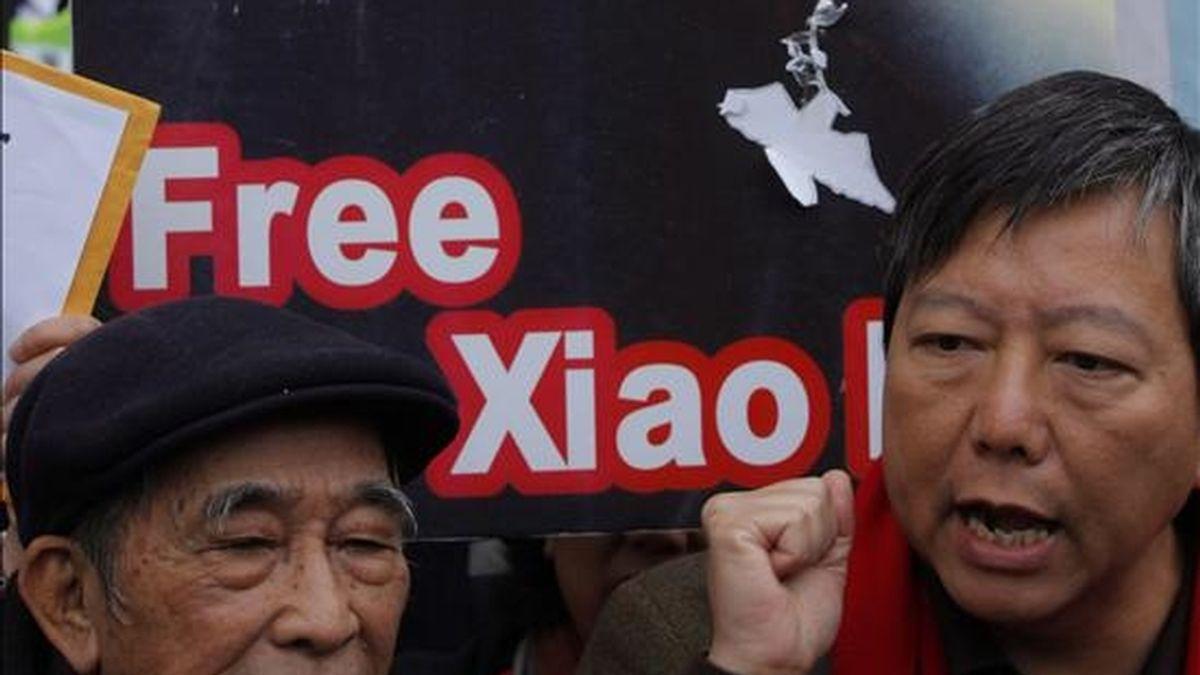 Fotografía del 28 de diciembre de 2009 del jefe del Movimiento de la Alianza de Apoyo Patriótico Democrático, Szeto Wah (izda), Szeto Wah, sosteniendo una imagen del disidente chino Liu Xiaobo durante una protesta en Hong Kong (China). Wah murió ayer, 2 de enero, a los 79 años debido a un cáncer de pulmón. EFE/Archivo