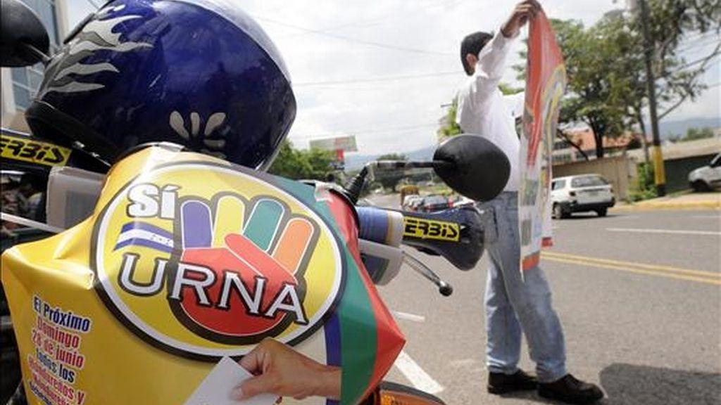 Un ciudadano hondureño muestra una pancarta, en Tegucigalpa (Honduras). El gobernante Partido Liberal pidió este sábado a los hondureños no participar en la consulta convocada para el próximo domingo por el presidente Manuel Zelaya. EFE