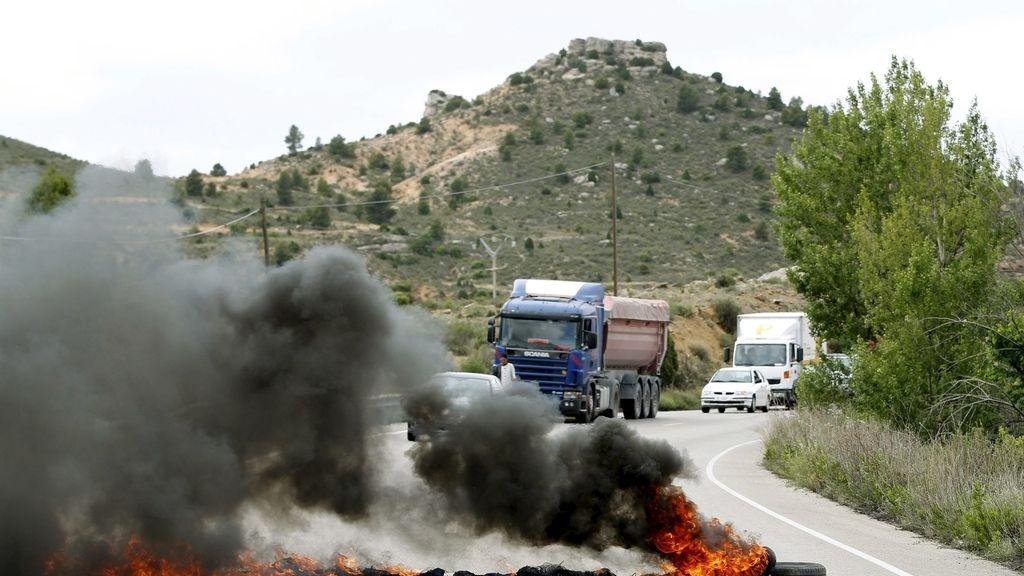 Una barrera compuesta por neumáticos incendiados, colocadas por un grupo de mineros para bloquear el suministro de carbón de importación a la Central térmica de Endesa en Andorra (Teruel), impide el paso de vehículos en las carretera entre Andorra y Ariño.