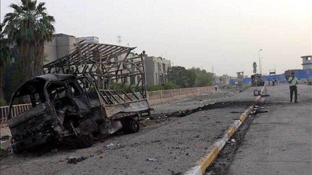 Un iraquí pasa junto a un vehículo quemado en el lugar donde explotó un coche bomba en el barrio de Al-Amil, al sur de Bagdad. EFE/Archivol
