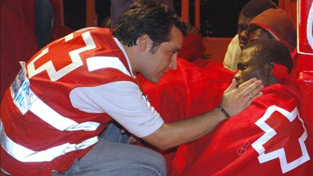 Un miembro de la Cruz Roja se interesa por el estado de uno de los 38 inmigrantes que llegó al puerto de Almería tras ser rescatados de la patera en la que viajaban por Salvamento Marítimo, el verano pasado. EFE/Archivo