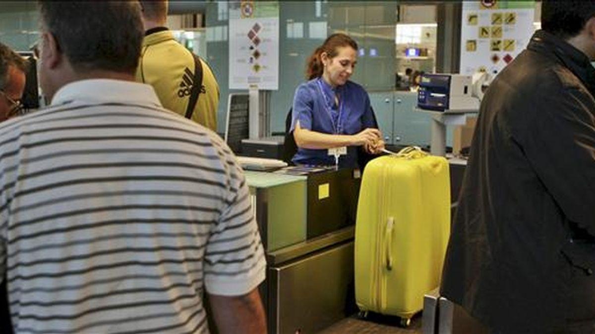 Varios pasajeros hacen cola frente a los mostradores de facturación en el aeropuerto del Prat de Llobregat (Barcelona) para volar, después de que el espacio aéreo español se haya reabierto tras el cierre que sufrió ayer cuando los controladores abandonaron masivamente sus puestos de trabajo. EFE