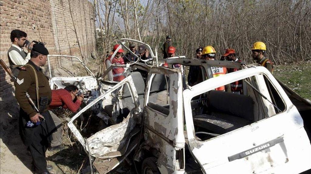 Miembros de las Fuerzas de Seguridad paquistaníes inspeccionan los daños causados a un vehículo escolar tras la explosión de un artefacto accionado por control remoto en Bashira, Peshawar (Pakistán). EFE