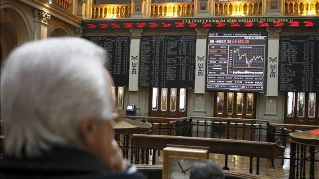 Varios operadores de la Bolsa de Madrid, ante el panel del ÍBEX 35. EFE/Archivo