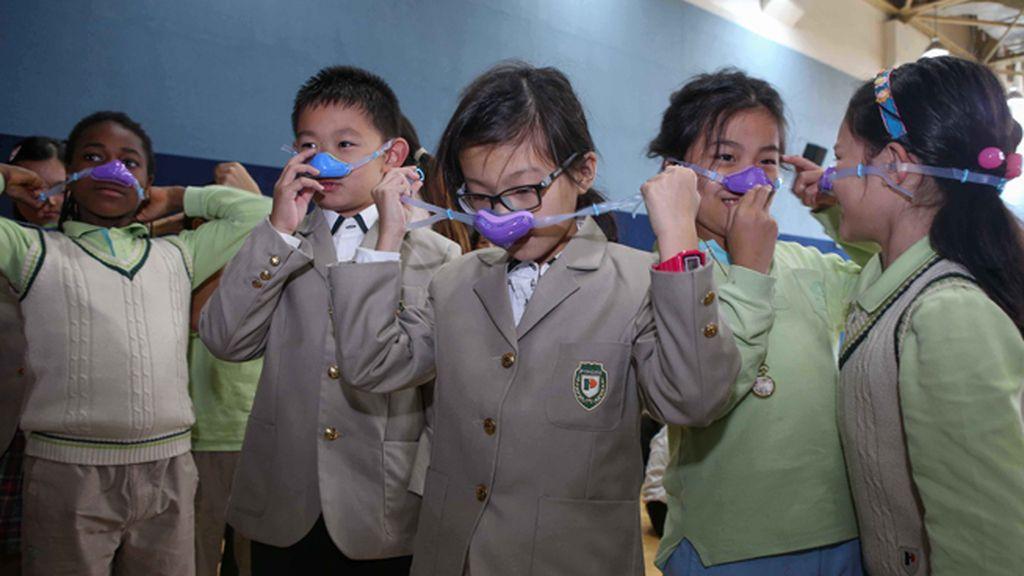 Niños con máscaras nasales por la contaminación en Shangai