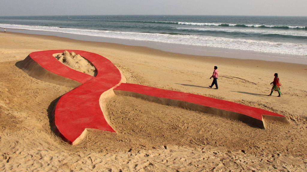 Escultura de lazo rojo en la playa