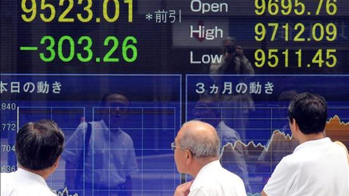 Varios hombres observan el tablero indicador del Nikkei en el centro de Tokio (Japón). EFE/Archivo