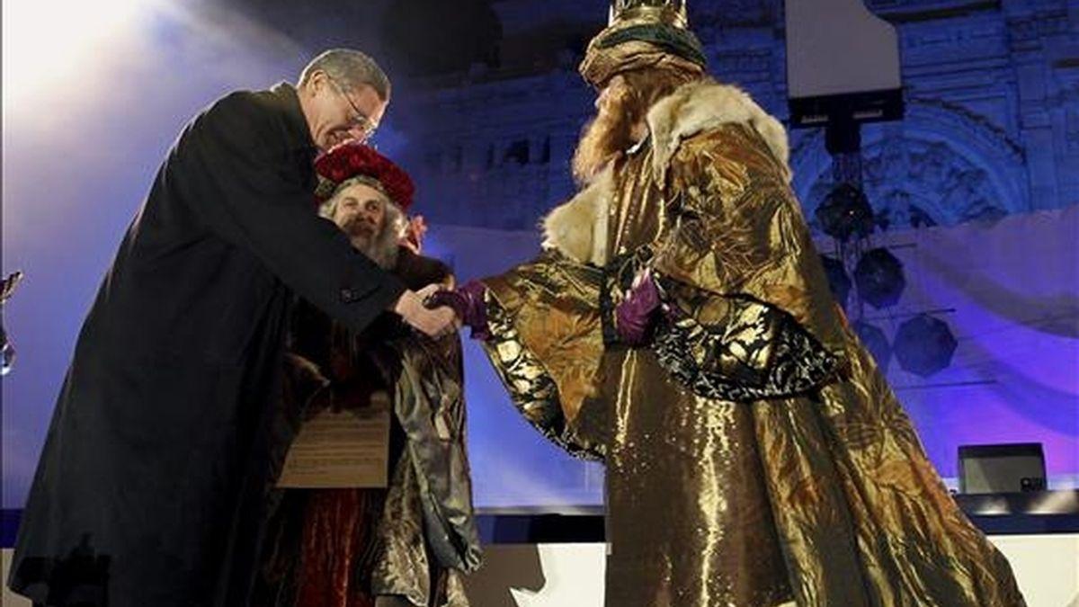 El alcalde de Madrid Alberto Ruiz Gallardón (i) saluda a los Reyes Gaspar (d) y Melchor en el escenario instalado en la plaza de Cibeles. EFE