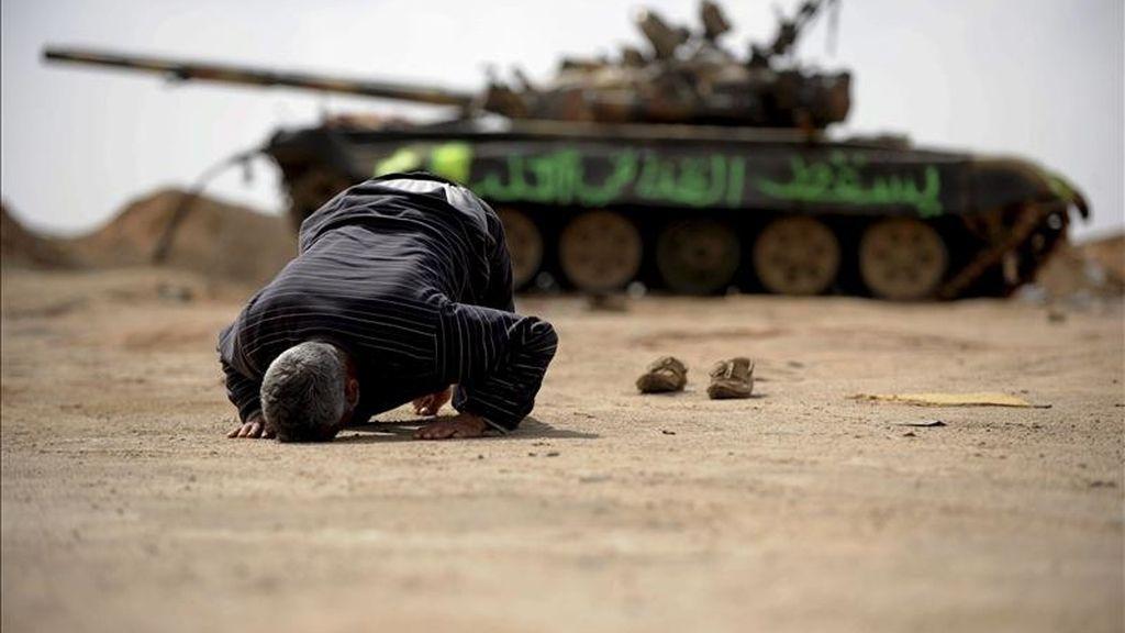 Un insurgente libio reza junto a los restos de un tanque destruído en las proximidades de Ajdabiya, Libia. EFE/Archivo