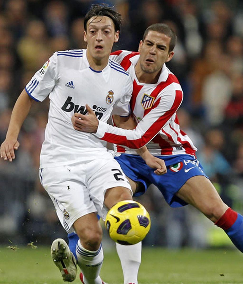 Özil le disputa un balón a Domínguez en el derby madrileño