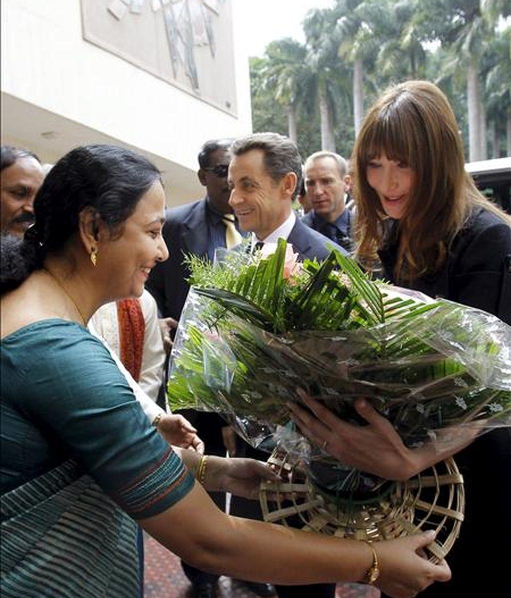 El presidente francés, Nicolás Sarkozy (c), junto a la primera dama francesa, Carla Bruni (d), que recibe un arreglo floral, llegan a una visita en la Organización india de Investigación Espacial (ISRO), en Bangalore (India), hoy, 4 de diciembre de 2010. EFE