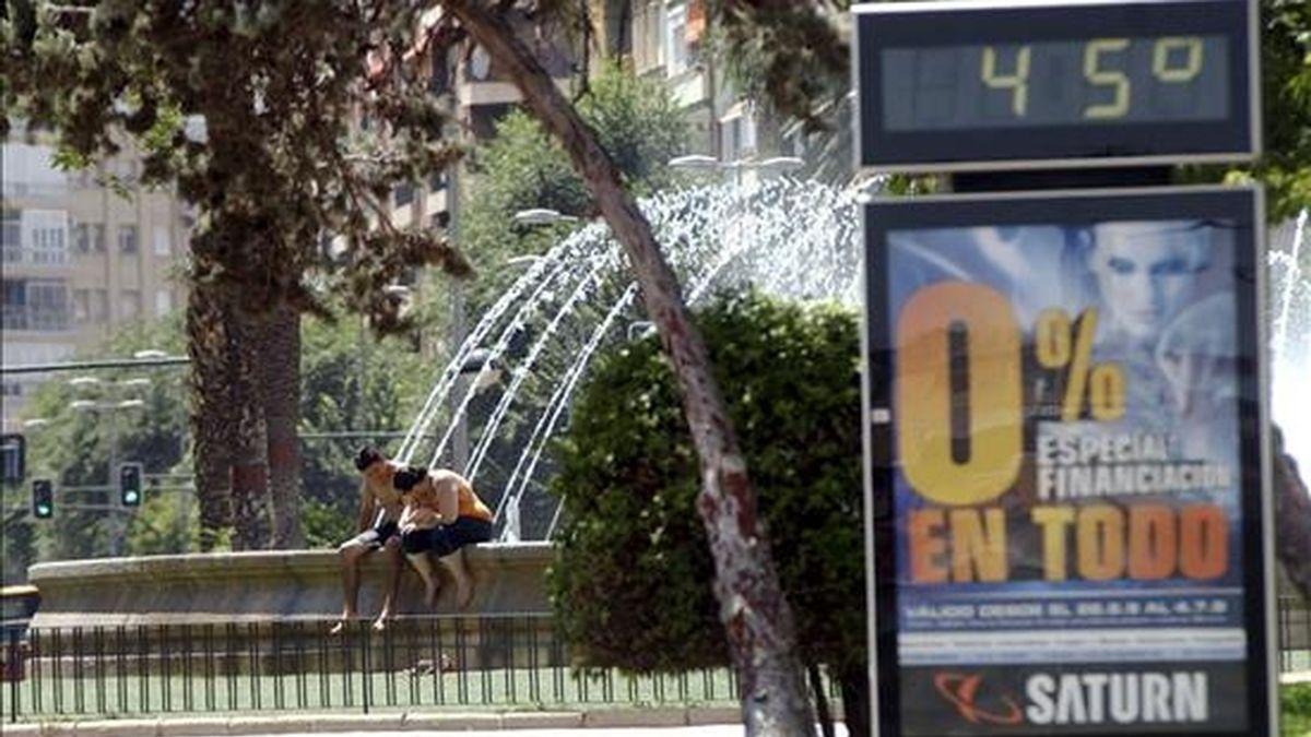 Dos jóvenes se refrescan en la fuente de la plaza circular de Murcia cerca de un temómetro de ambiente que marca 45 grados centigrados, coincidiendo con la entrada en alerta amarilla debido a las altas temperaturas. EFE/Archivo