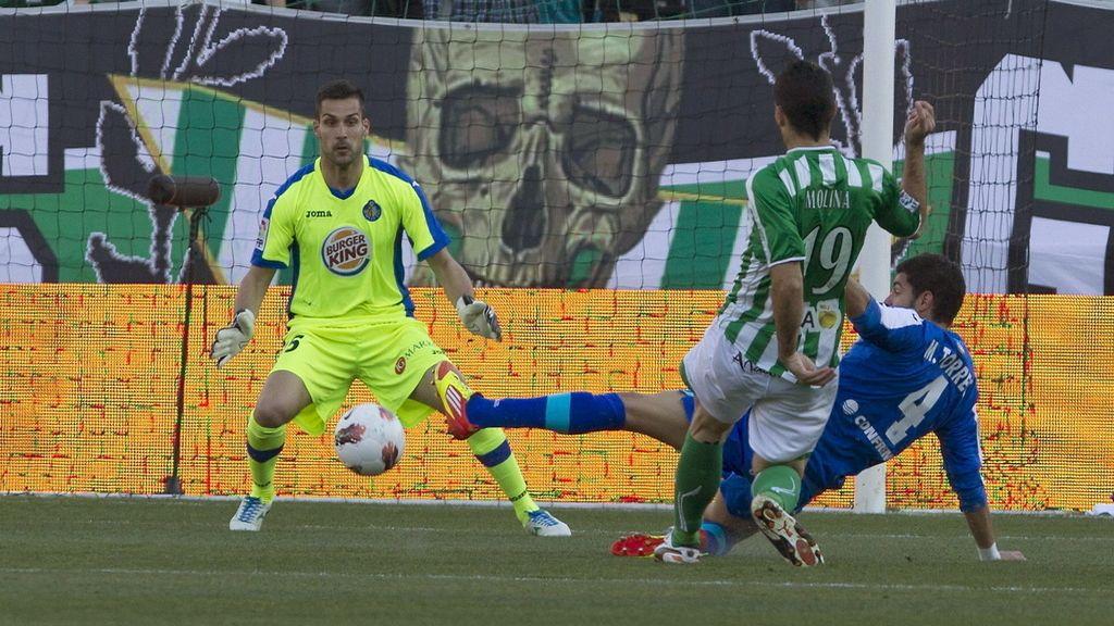 El delantero del Real Betis Jorge Molina chuta a portería ante el portero y el defensa del Getafe CF Miguel Ángel Moyá y Miguel Torres