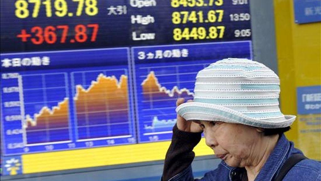 Una mujer camina cerca de un panel electrónico que muestra los valores de la bolsa de Tokio. EFE/Archivo