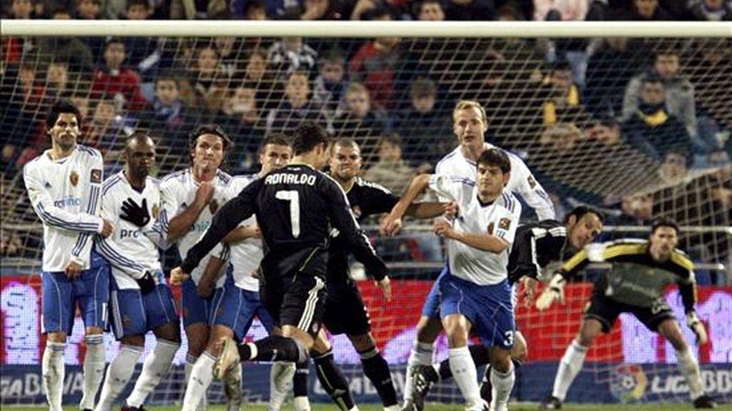 El delantero portugués del Real Madrid Cristiano Ronaldo (c) se dispone a lanzar la falta, que ha supuesto el segundo gol de su equipo, durante el partido correspondiente a la decimoquinta jornada de Liga que el conjunto madridista disputó con el Real Zaragoza en el estadio La Romareda. EFE