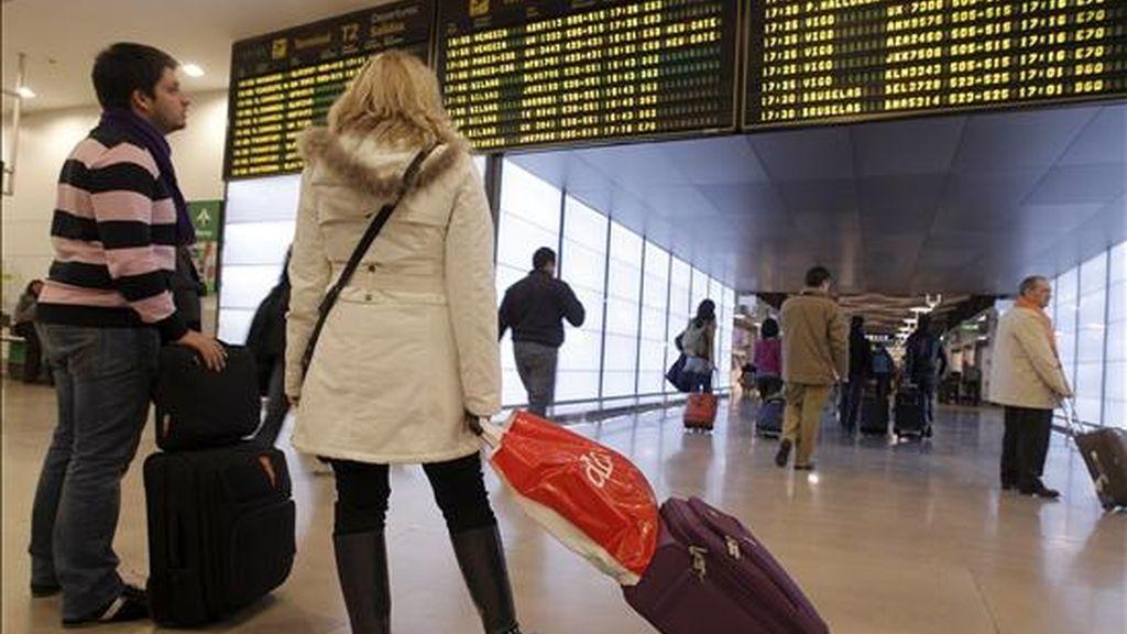 Dos pasajeros contemplan los paneles informativos con la actividad de los vuelos del aeropuerto de Barajas (Madrid), que a lo largo de la jornada de hoy ha recuperado a normalidad, con una masiva presencia de los controladores convocados al trabajo y la salida de numerosos vuelos. EFE