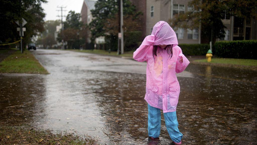 Una niña juega en la calle durante el paso del huracán