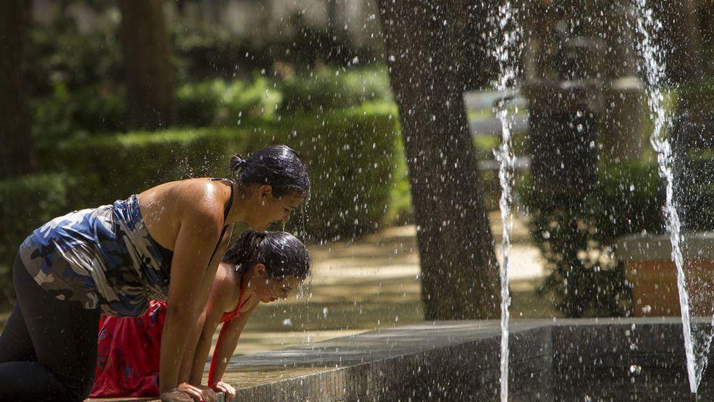 Dos jóvenes se refrescan en una fuente en Sevilla