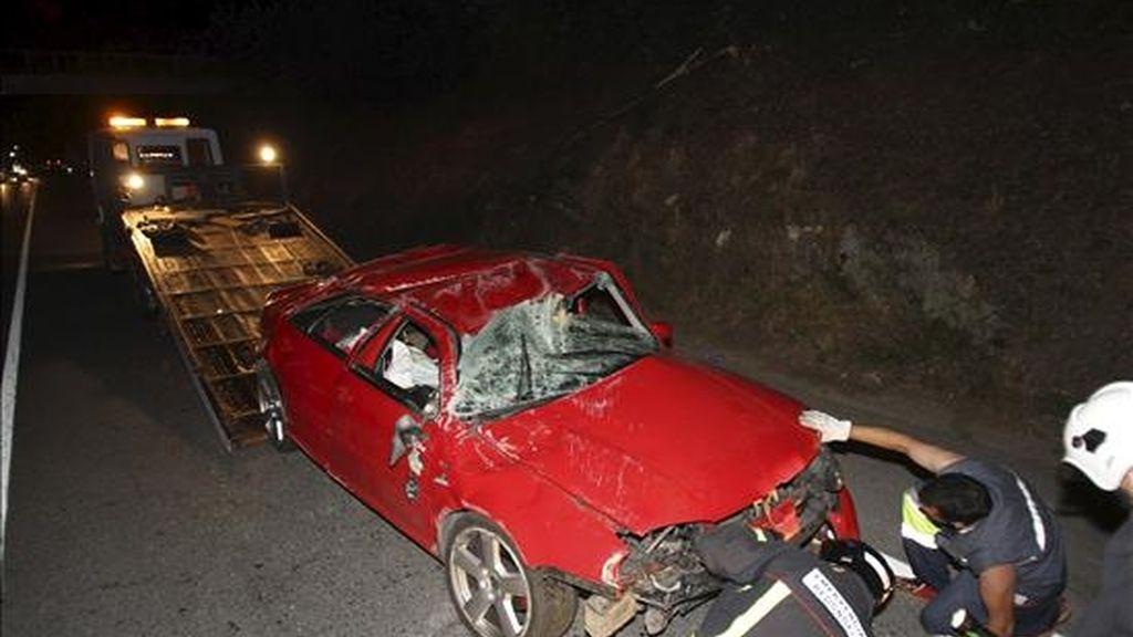 Los bomberos retiran el vehículo donde dos jóvenes resultaron gravemente heridos esta madrugada tras caer por un precipicio en el municipio pontevedrés de Redondela. EFE