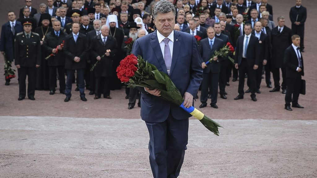 El presidente ucraniano, Petro Poroshenko (c), deposita flores en el monumento de las víctimas de la masacre Nazi en Babi Yar, en Kiev