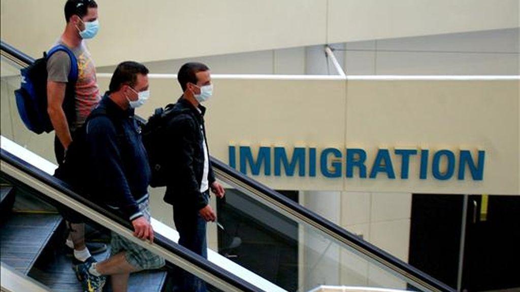 Tres pasajeros con mascarillas caminan por el aeropuerto internacional de Brisbane (Australia). EFE/Archivo