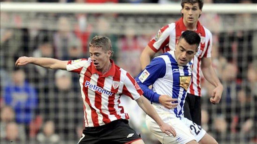 El delantero del Athletic de Bilbao, Iker Muniain (i), defiende un balón frente al centrocampista argentino del Espanyol, Aldo Duscher (d), durante el partido correspondiente a la decimoquinta jornada de Liga en Primera División en el estadio San Mamés de Bilbao.EFE