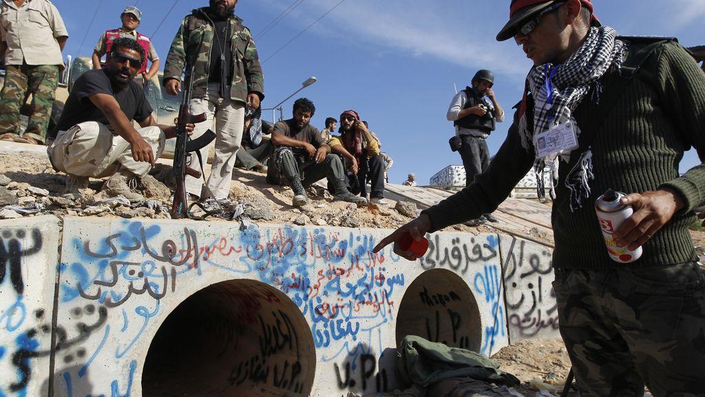 Un miembro de las fuerzas del CNT señala el zulo en el que se escondía Gadafi