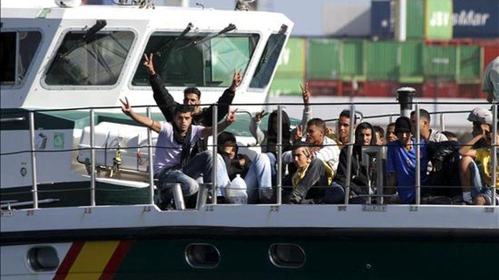 Varios de los treinta inmigrantes, algunos menores de edad, que viajaban en una patera y que han sido interceptados por una patrullera marítima de la Guardia Civil, a su llegada hoy al Puerto de Naos, en Lanzarote, donde ha sido atendidos por personal de Cruz Roja. EFE