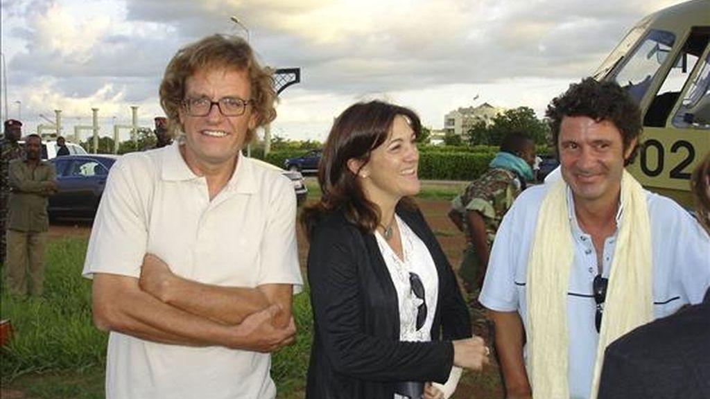 Los cooperantes españoles Albert Vilalta (d) y Roque Pascual (i), liberados tras casi nueve meses de secuestro por Al Qaeda en el Magreb Islámico (AQMI), acompañados por la secretaria de Estado de Cooperación Internacional, Soraya Rodríguez, a su llegada en helicóptero Uagadugú, capital de Burkina Faso. EFE