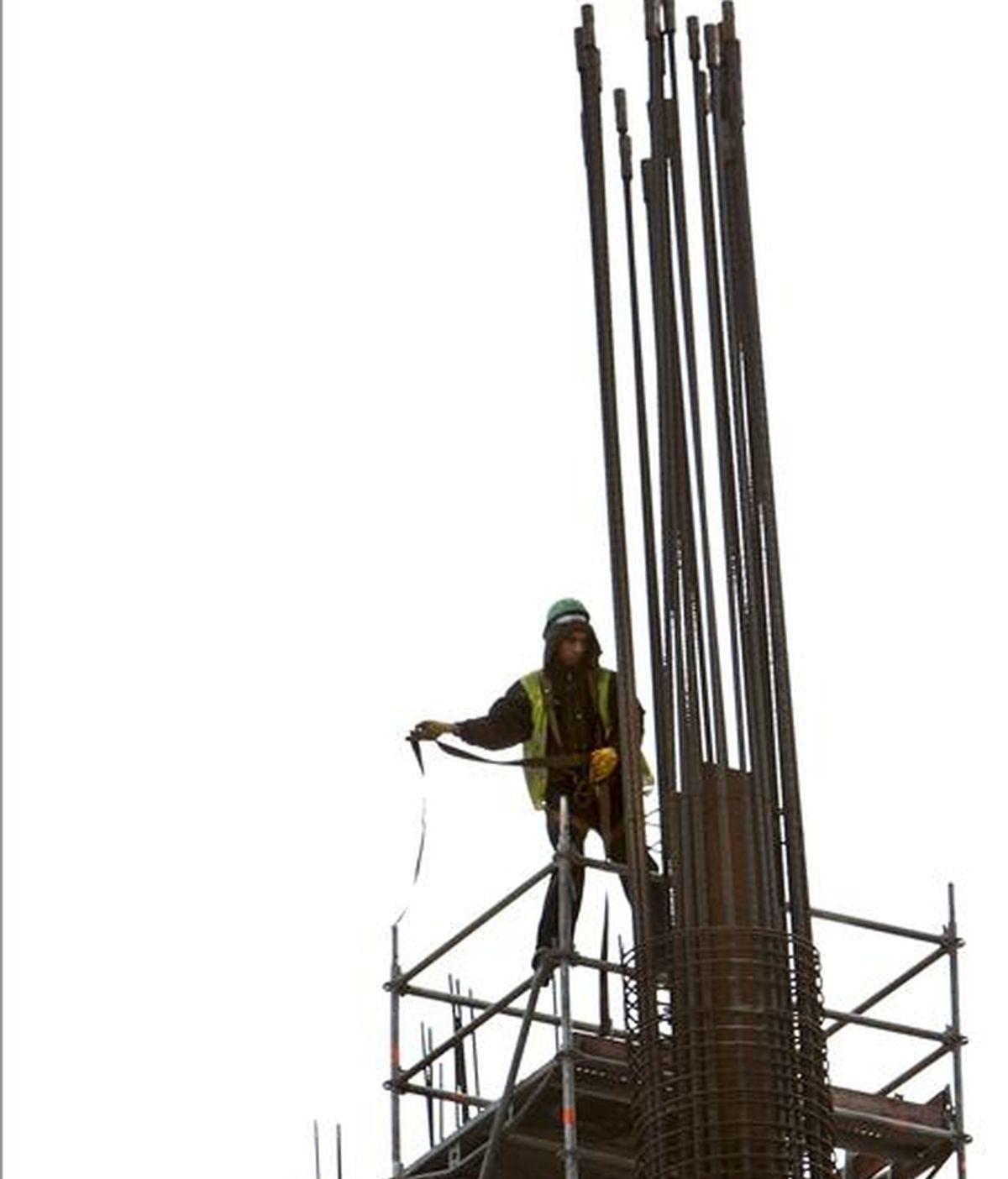 Un trabajador de la construcción intenta asegurarse con su arnés en una obra. EFE/Archivo