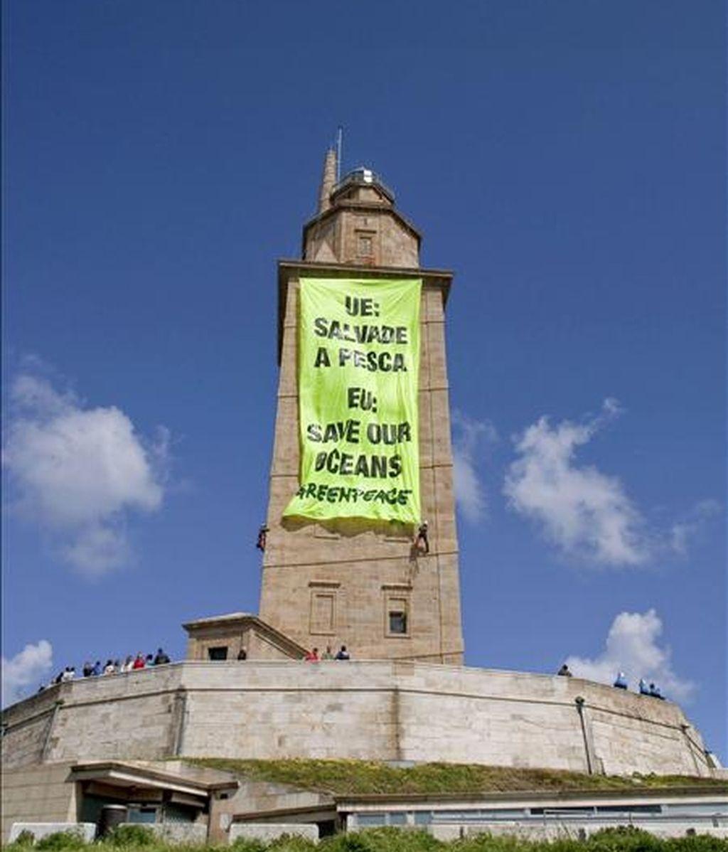 """Miembros de la organización ecologista Greenpeace han desplegado esta mañana en la Torre de Hércules de A Coruña, monumento romano declarado recientemente Patrimonio de la Humanidad, una pancarta de unos 200 metros cuadrados donde se podía leer el mensaje """"UE: Salvad la pesca"""". EFE"""