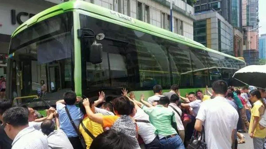 Decenas de turistas y ciudadanos colaboran para salvar a una anciana atrapaba bajo un autobús en China