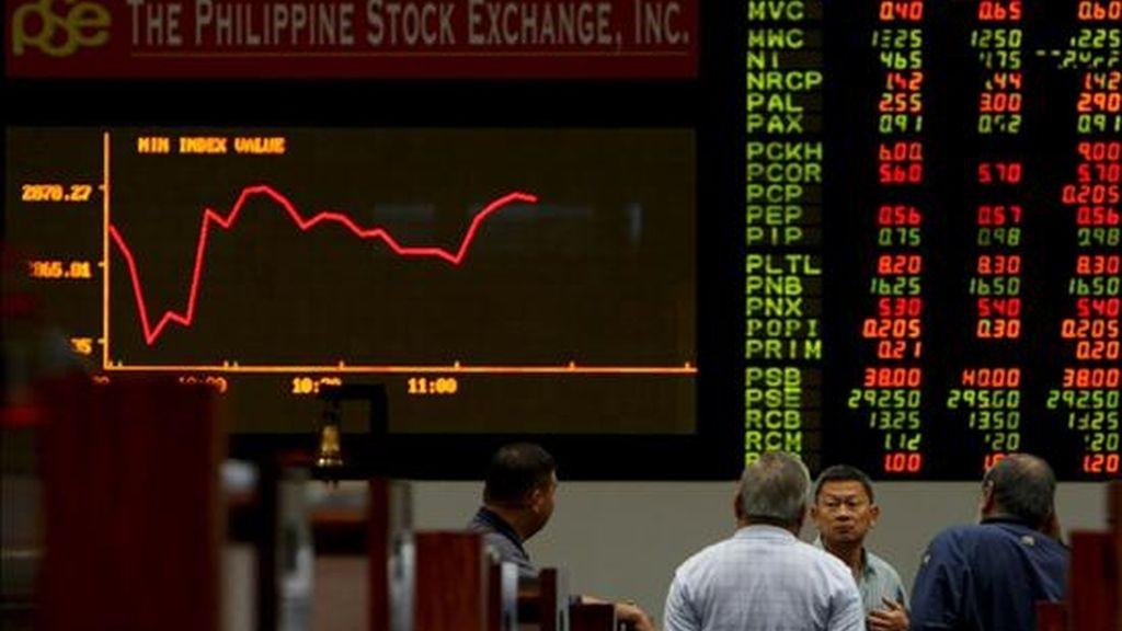 Varios agentes conversan junto a un panel electrónico en el que se muestran las operaciones de Bolsa, en el parqué de Manila (Filipinas). EFE/Archivo