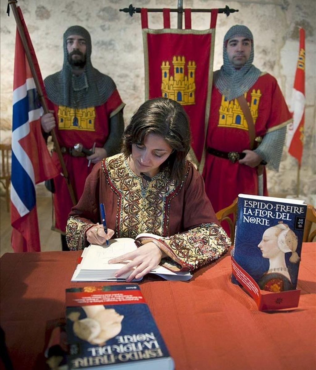 La escritora Espido Freire firma un ejemplar durante la presentación de su novela 'La flor del Norte', una biografía sobre la princesa Cristina de Noruega que fue enterrada en Covarrubias. EFE