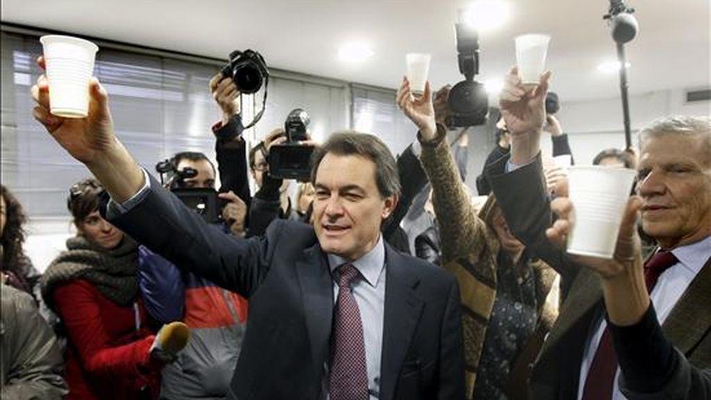 El líder de Convergencia i Unió ( CiU ), Artur Mas, vencedor en las elecciones autonómicas celebradas ayer, brindando a su llegada esta mañana a la sede de esa fuerza política. EFE