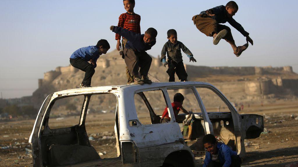 Niños afganos juegan en un coche destruído