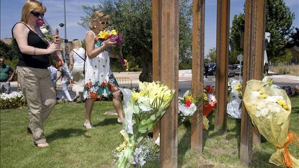 Dos familiares de algunas de las once víctimas del incendio de la Riba de Saelices (Guadalajara) depositan flores en el monumento inaugurado en su recuerdo al cumplirse el quinto aniversario del suceso. EFE