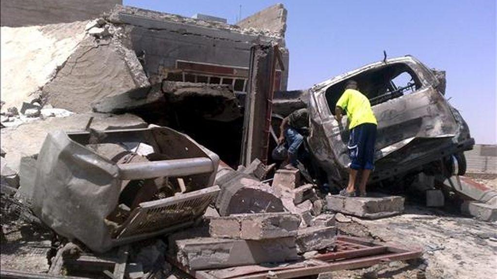 Dos niños iraquíes observan los restos de un vehículo y de una casa tras la explosión de una bomba, en Ramadi, capital de Anbar, Irak, el 8 de julio de 2010. EFE/Archivo
