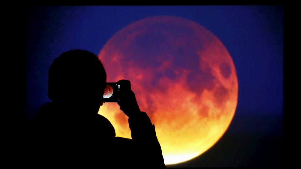 Un hombre hace una fotografía de la 'superluna' en Warsaw, Polonia