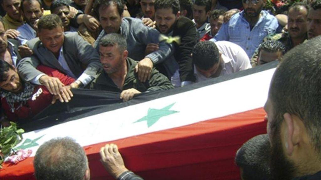 Fotografía facilitada por la agencia SANA que muestra el funeral de uno de los policías fallecidos ayer quien, según autoridades sirias, murió a nabis de un grupo terrorista armado en Homs (Siria) hoy, sábado, 7 de mayo de 2011. Los funerales de las víctimas en la revuelta de ayer en Siria, que coinciden con nuevas protestas, empezaron hoy en Homs y Hama, donde murieron al menos 21 personas, según un activista de derechos humanos. EFE