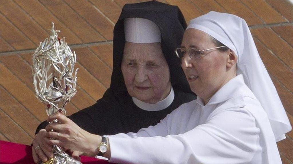 Las hermanas Tobiana (d) y Marie Simon Pierre tocan el relicario que contiene la sangre del papa Juan Pablo II, durante la ceremonia de beatificación oficiada por el papa Benedicto XVI, hoy en la plaza de San Pedro del Vaticano. EFE