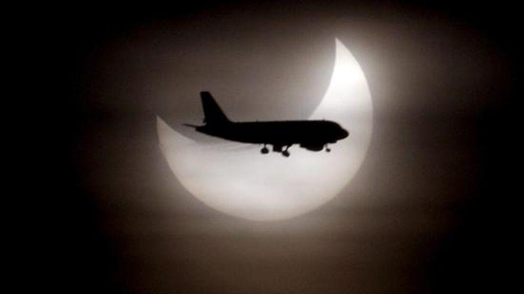 Un avión pasa ante el sol durante el eclipse solar parcial que se ha producido a primera hora de esta mañana y que en Barcelona se ha visto deslucido por la presencia de nubes. EFE