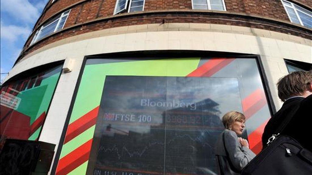 Una mujer pasa por delante de un panel electrónico en el que se muestran los valores de la Bolsa, en Londres (Reino Unido). EFE/Archivo