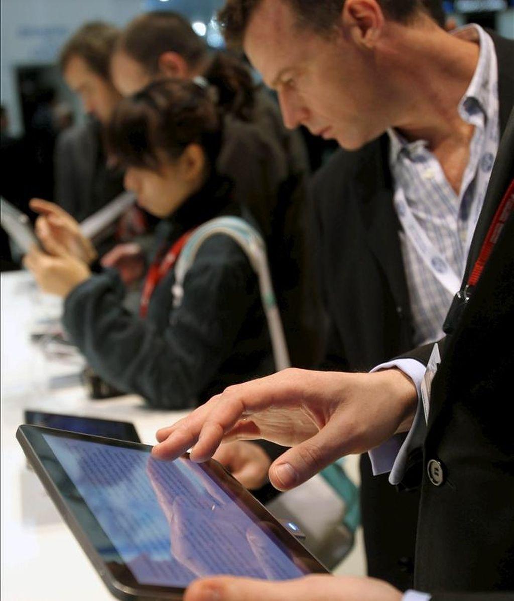 Varias personas examinan las nuevas tecnologías que se exponen en la edición de este año del Mobile World Congress de Barcelona. EFE/Archivo