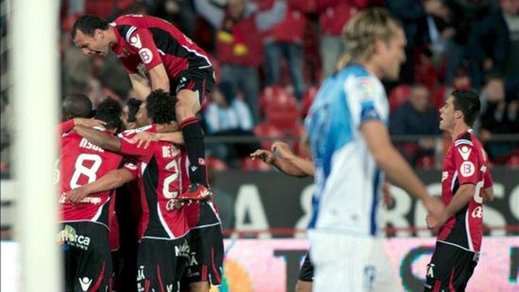 Los jugadores del RCD Mallorca celebran el segundo gol ante el Málaga CF, conseguido por el centrocampista uruguayo Gonzalo Castro 'Chori Castro', durante el encuentro correspondiente a la decimotercera jornada de Liga en Primera División que ambos conjuntos han disputado esta tarde en el Iberostar estadio de la capital balear. EFE