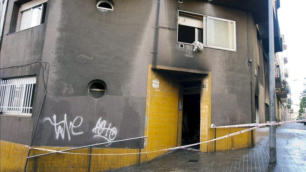 Un cordón policial a la entrada de un edificio de viviendas ubicado en el número 41 de la calle Mas de L'Hospitalet de Llobregat, donde se ha declarado hoy un incendio en el que han resultado heridas siete personas, dos de ellas de gravedad. EFE