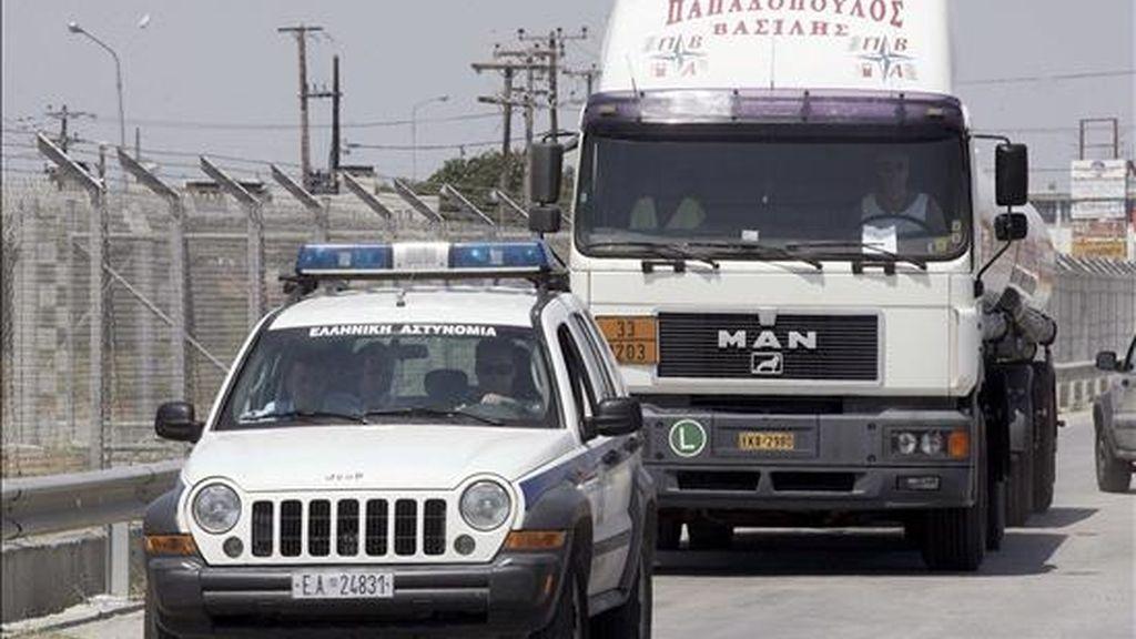 Un camión cisterna es escoltado por la policía a su salida de una refineria a las afueras de Tesalónica (Grecia). EFE