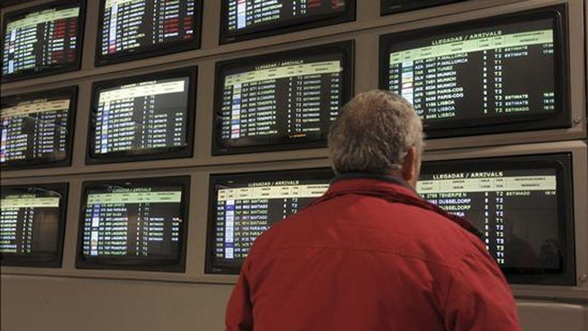 Un hombre contempla las pantallas informativas con la actividad de los vuelos del aeropuerto de Barajas (Madrid), ayer. EFE