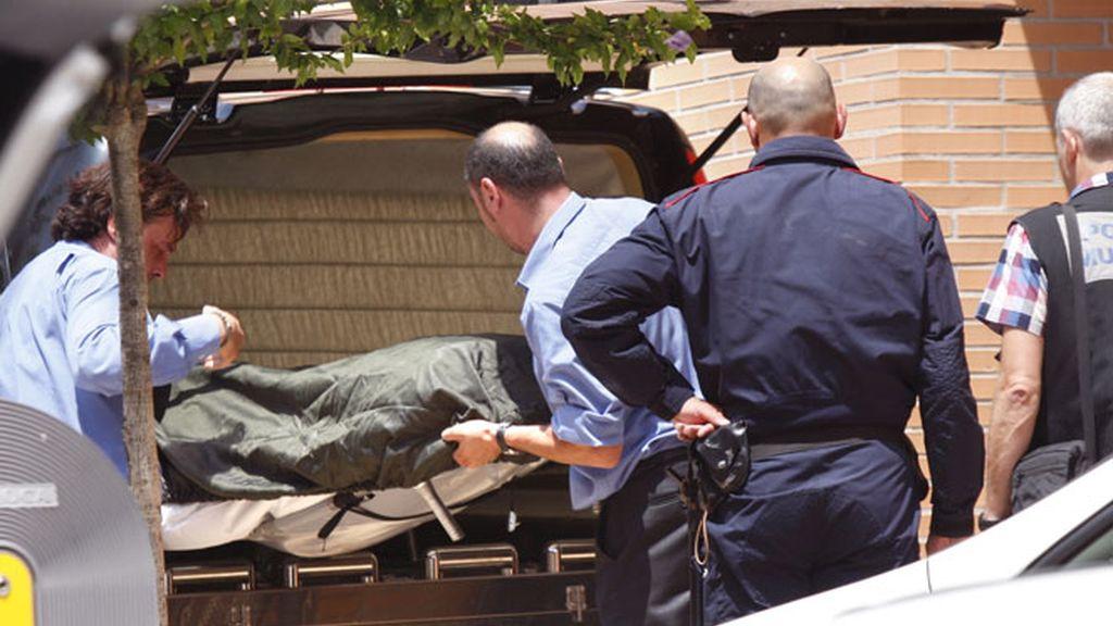 Empleados de la funeraria trasladan el cuerpo de la mujer y el menor asesinados